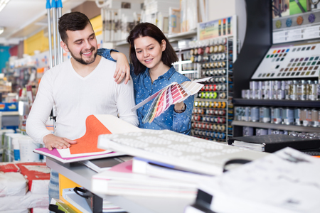 coatings: Smiling couple examining various decorative materials at paint supplies store. Focus on woman