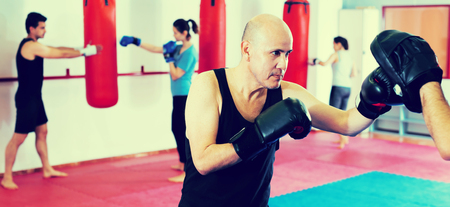 pugilist: Two male athletes in sportswear practicing boxing sparring at sport class