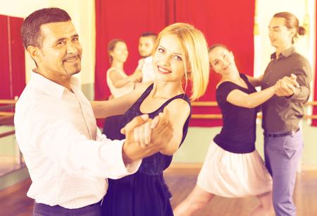 Happy elegant adults  enjoying of classical dance in class 스톡 콘텐츠