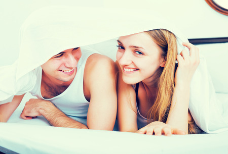 Smiling young couple lying in family bed under sheet