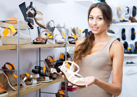 Smiling young female customer showing desired shoe in boutique Stock Photo