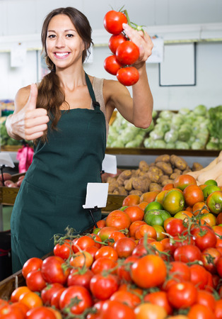 friendly smiling young woman seller showing fresh ripe tomatoes in food store
