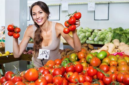Glad positive smiling woman picking fresh tomatoes on fruit market Stock Photo