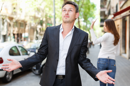 Quarrel between loving couple strolling on city streets