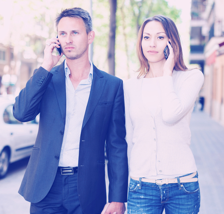 Young couple strolling together and ignoring each other speaking on phones