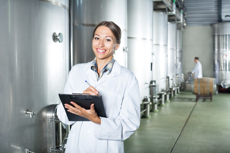 Young cheerful woman wearing coat taking notes in secondary fermenting section at wine factory Stock Photo