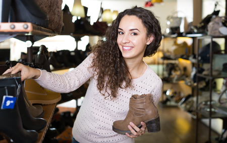 Smiling young longhaired brunette buying fashion winter shoes in a shoe store