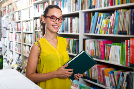 Positive young woman taking literature books in store with prints Stock Photo