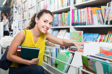 publishers: Young glad woman buying books in hard cover in bookstore