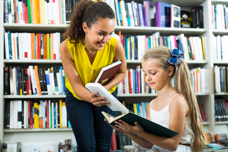portrait of smiling glad woman giving to girl literature books in store with prints. Focus on girl