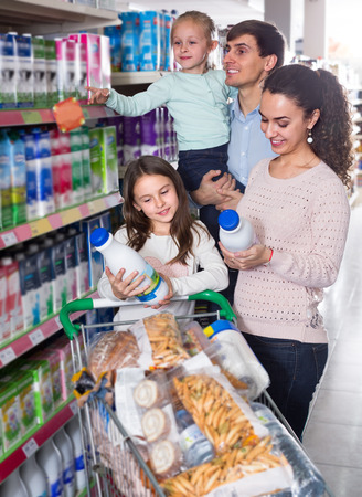 family with two daughters purchasing kefir in supermarket