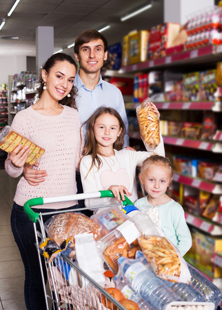 shortbread: Attractive customers with small children purchasing shortcakes in hypermarket and smiling Stock Photo