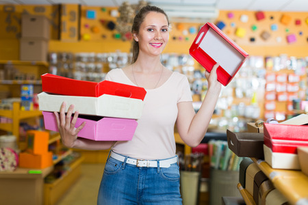 smiling woman shows bright boxes for gifts in a store Stock Photo