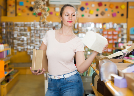 Beautiful girl with gift boxes in her hands chooses accessories for gift in store Stock Photo
