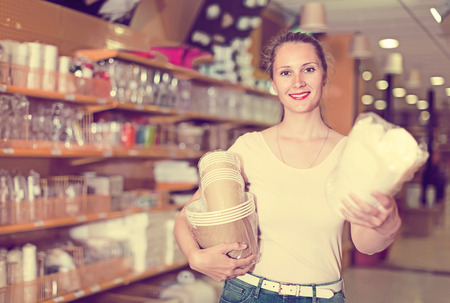 Brunette girl with disposable tableware in her hands chooses disposable tableware in store Stock Photo
