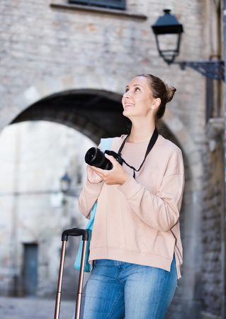 Young girl holding camera in hands and photographing at a city