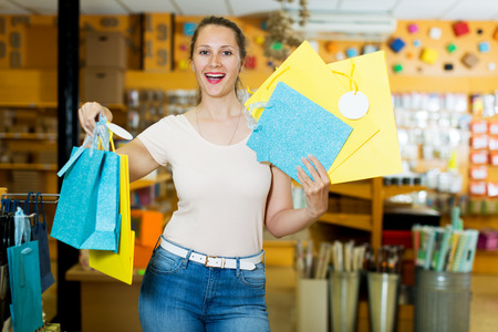 pasteboard: Portrait woman demonstrates multi colored and other gift bags