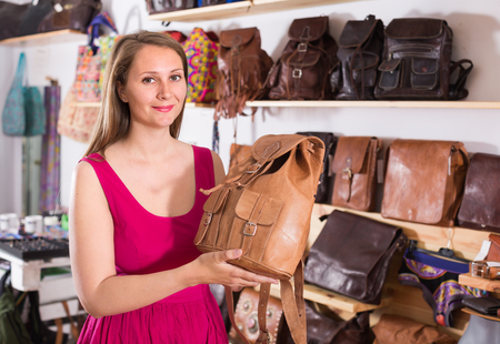 happy french adult female in shopping mall choose backpack Stock Photo