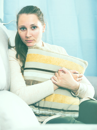 cuddled: Young woman feeling distressed and lonely alone at home