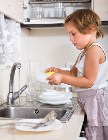 Happy cute baby girl washing dishes at domestic kitchen