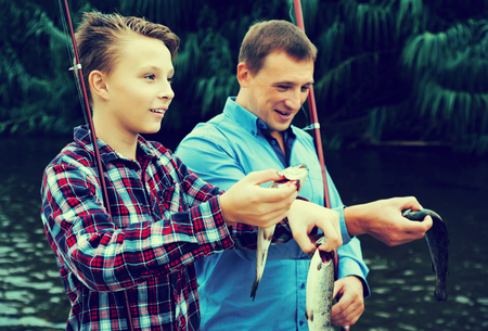 gills: Smiling teenage boy and his father holding taken freshwater fish in  hands