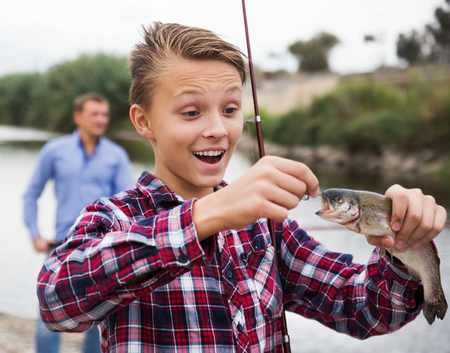 gills: Glad teenager boy holding and looking at a fish on a hook