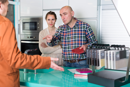 Adult couple dissatisfied with the quality of the goods in kitchen furniture  store Stock Photo