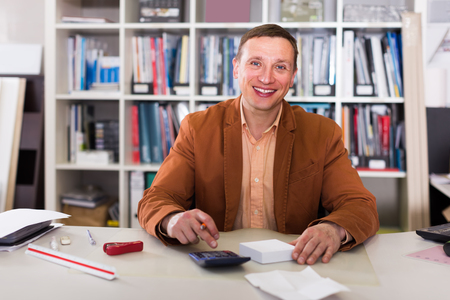 Portrait of smiling manager working at the table in agency office