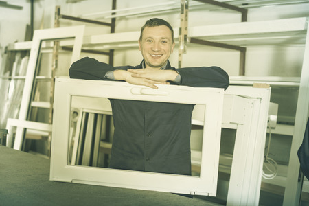 toolroom: Smiling adult professional labours with finished PVC profiles and windows at factory