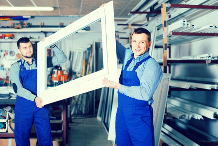 completed: Production smiling workers in coverall with different    finished PVC profiles and windows at factory Stock Photo