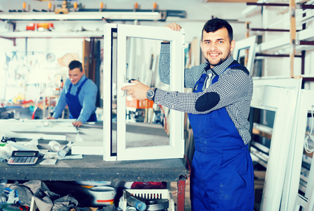 toolroom: Young guy worker is demonstrating the window frame in workshop.