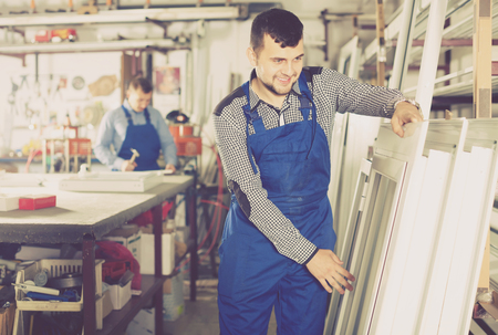 young professional labours with finished PVC profiles and windows at factory Stock Photo