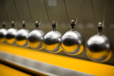 energy channels: Line of metallic globes for Cartesian impulse conservation law experiment Stock Photo