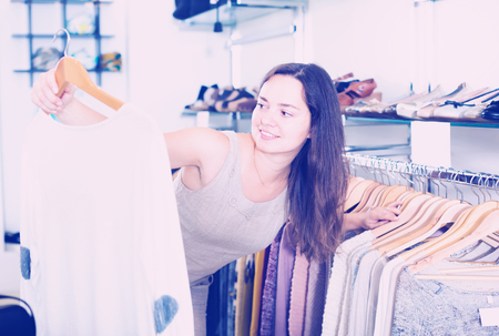 suitable: smiling woman choosing new long sleeve blouse in apparel shop