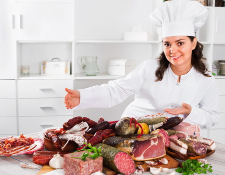 Young positive girl cook costs near table on which sausages and smoked meat lie