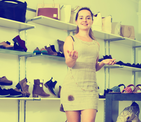 portrait of cheerful female seller with dark hair working in shoes store Stock Photo