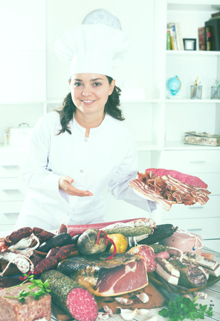 Young girl in uniform holds in hand plate with cut by the jamon and a sausage