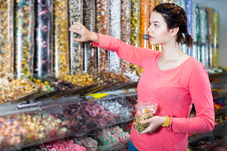 shopkeeper: Young female is choosing candies in shop. Stock Photo