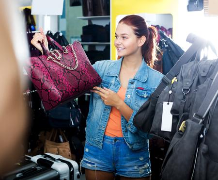 Portrait cheerful teenager girl buying handbag in fashion shop Stock Photo