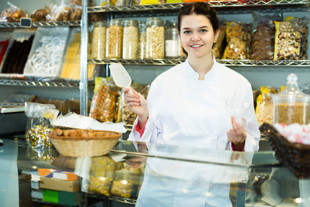 Young saleswoman is pouring on candied fruit into bag in the shop. Stock Photo