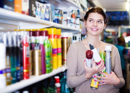 Smiling young female customer looking for hair care products in cosmetics shop