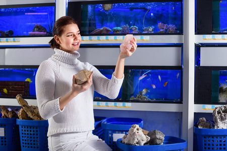 aquarian: Positive girl at aquarium store choosing interesting stones, rocks and corals for aquarium installation