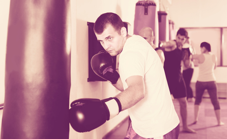 pugilist: Male boxer is beating a boxing bag in the boxing hall.