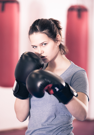 Young girl practicing different kiks in the boxing hall Stock Photo