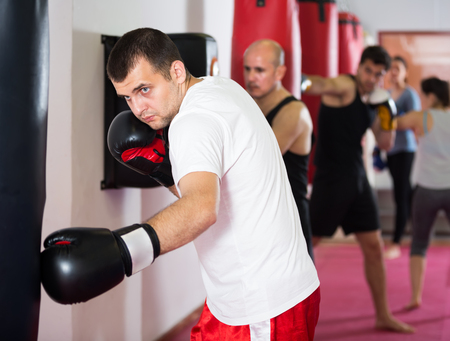sportsman in the boxing hall practicing boxing punches with boxing bag during training Stock Photo