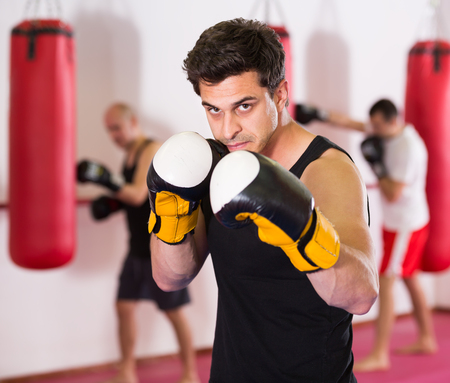 vigorous sportsman in the boxing hall practicing boxing punches during training