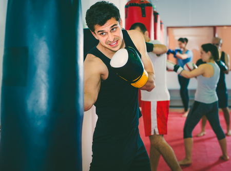 pugilist: active sportsman in the boxing hall practicing boxing punches with boxing bag during training