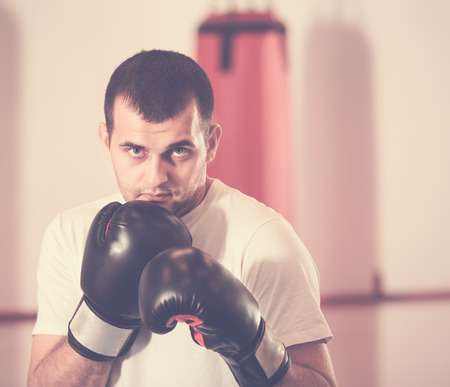russian ethnicity: attentive sportsman in the boxing hall practicing boxing punches during training