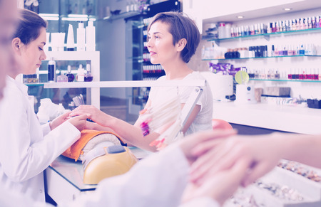cheerful female manicurist filing and shaping nails during procedure of manicure in beauty salon Stock Photo