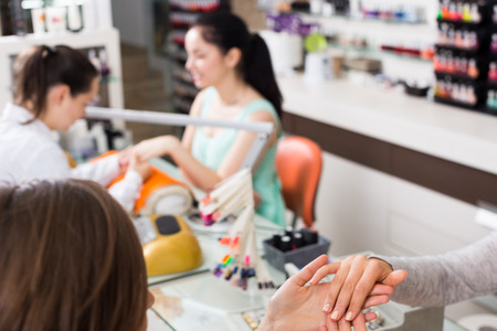 Closeup of manicurist inspecting female hands and nails in beauty salon Stock Photo